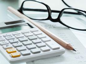 Rechercheunterlagen mit Taschenrechner, Stift und Zetteln.